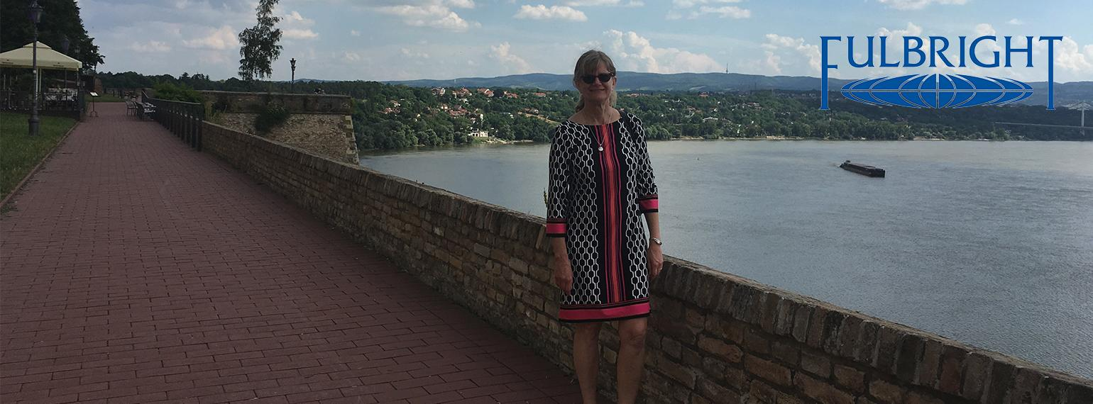 Dr. Zora Djuric stands on a brick sidewalk near a short brick wall on the banks of a river.