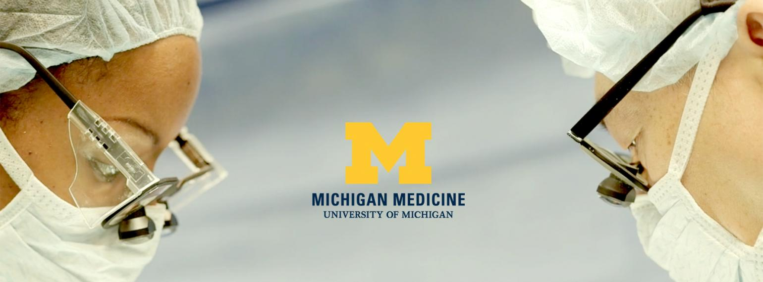 Dr. Chung and surgical team member in the operating room with the Michigan Medicine logo