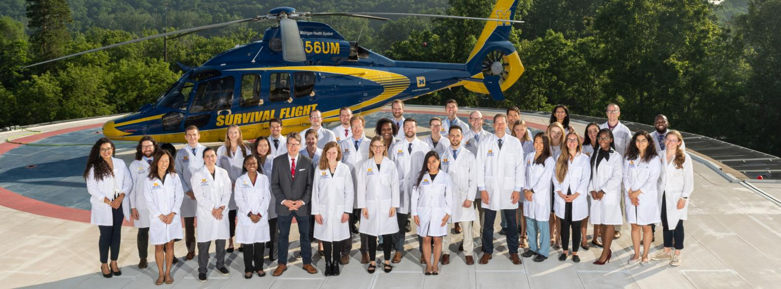 General Surgery residency leaders and trainees standing on helicopter pad with Survival Flight helicopter