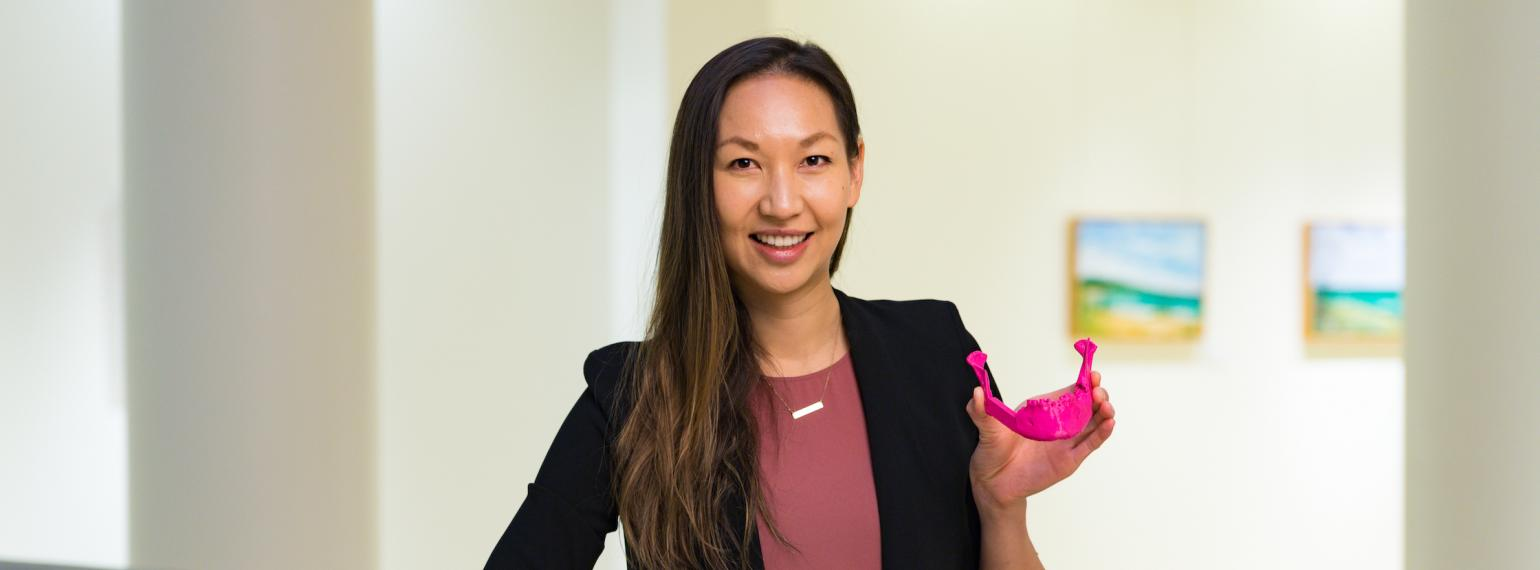 Dr. Justine Moe holding a model of a jaw