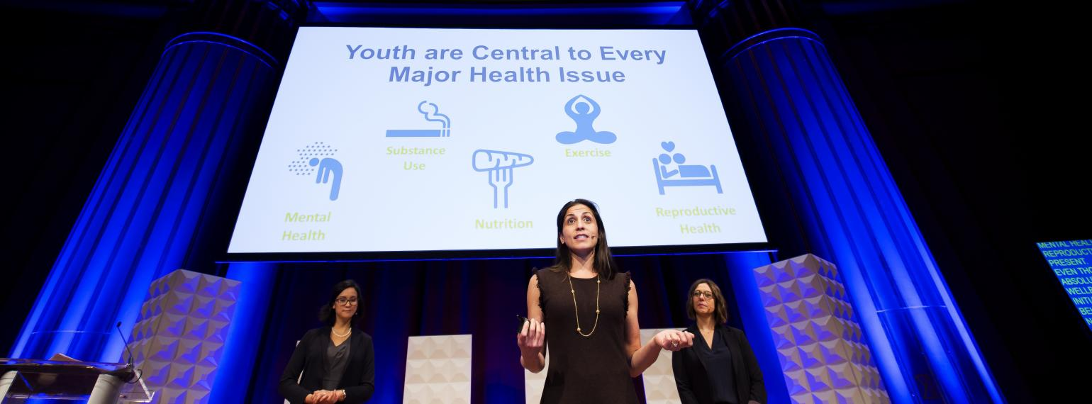 "MyVoice team presents TED talk at MCubed Symposium, with ""youth are central to every major health issue"" text on slide in background"