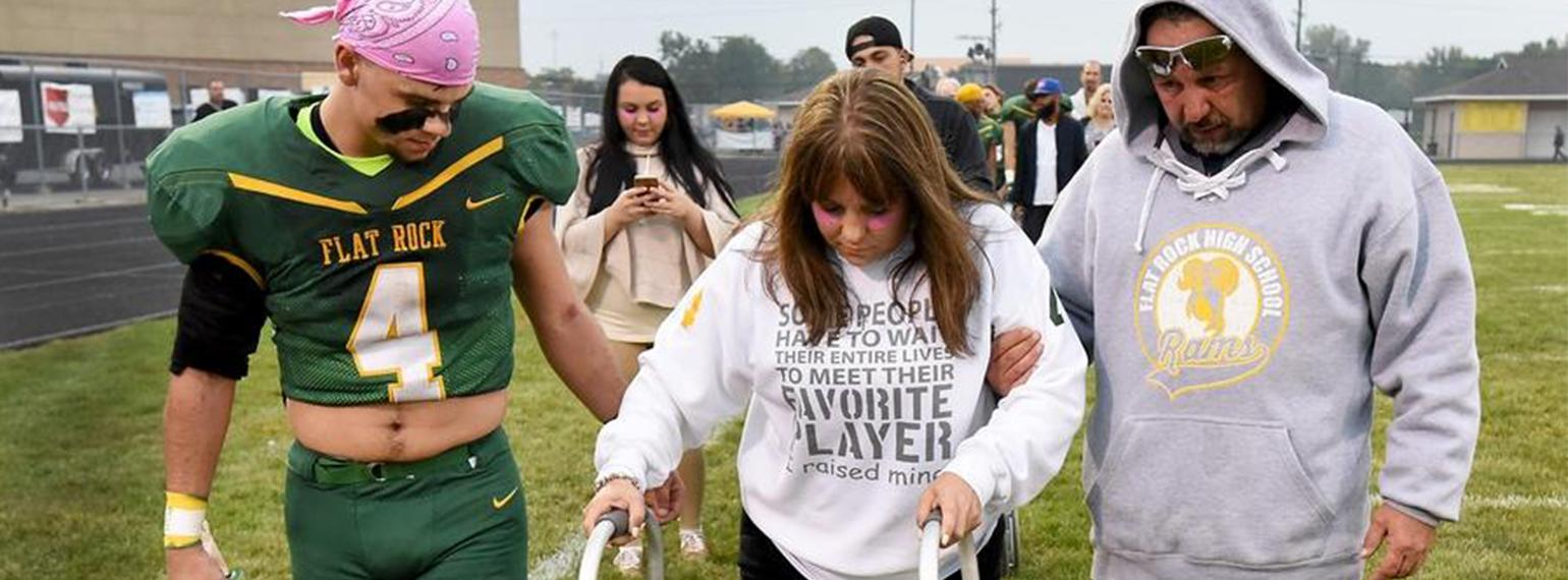 PM&R patient Lesley Daniels of Brownstown Township, whose legs were amputated walks with her son, Sage at his high school football game