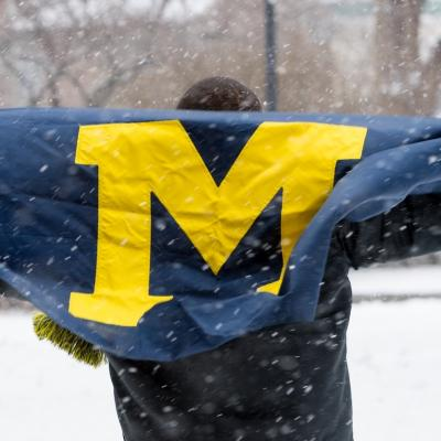 Student holding University of Michigan flag