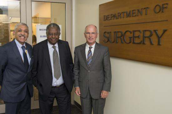Dr. Raghavendran, Dr. Debas, and Dr. Mulholland standing in front of the Department of Surgery sign at the Michigan Center for Global Surgery Launch Event.