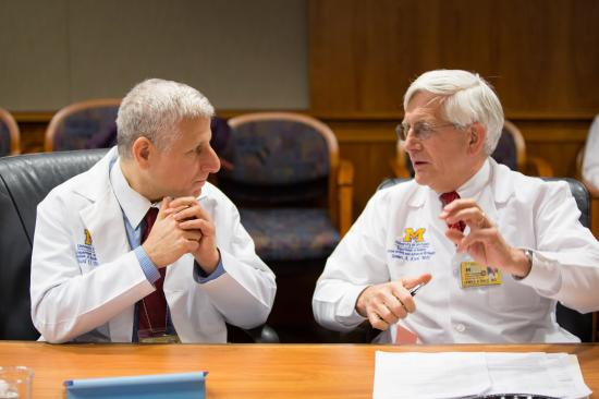 Photo of two physicians talking while sitting at at desk.
