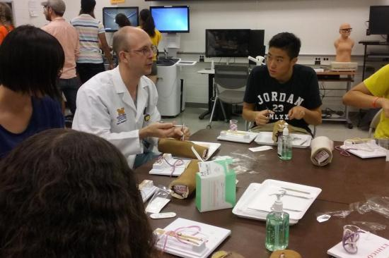 Students at table listening to instructor