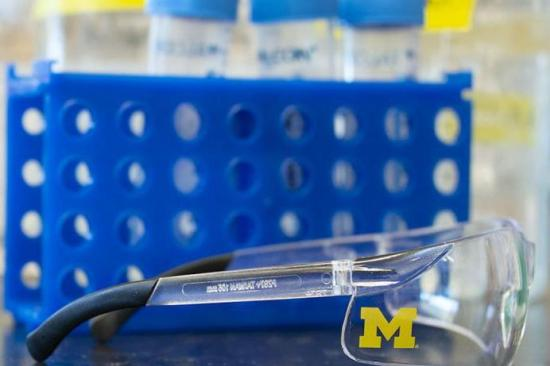 Pair of lab glasses with University of Michigan logo and lab equipment on counter