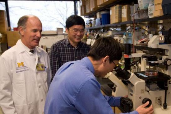 Dr. Mulholland and Dr. Zhang in the lab with a team member