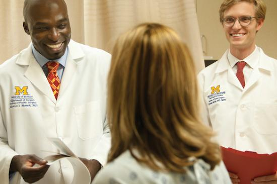 Dr. Momoh and Dr. Berlin talking to a patient in clinic