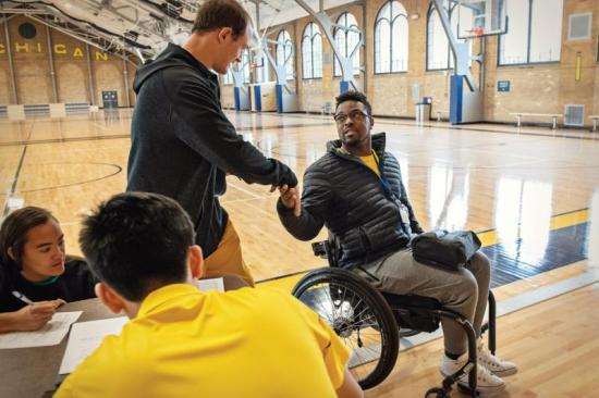 Dr. Okanlami shaking hands after wheelchair basketball practice