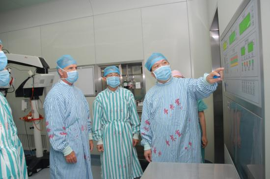 Dr. Mulholland and a group of surgeons discussing a display in China
