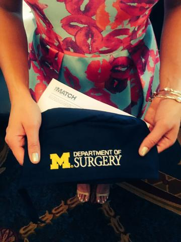 Dr. Valbuena holding a University of Michigan Surgery surgical cap on Match Day