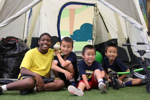 Kids and staff at the UMAISE adaptive camp pose in front of a tent