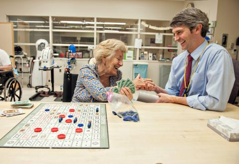 Dr. Ted Claflin playing cards with a stroke patient