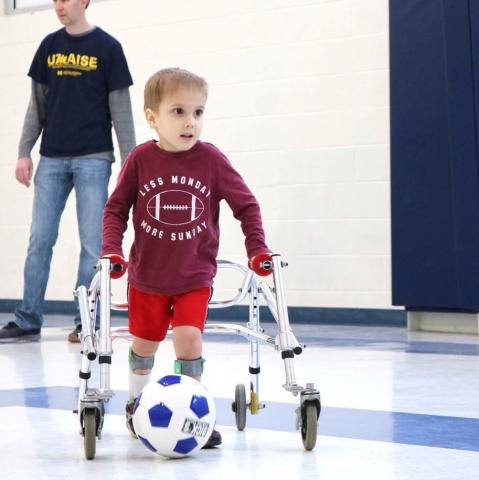 A photo of a young boy playing soccer with assistance of a walker