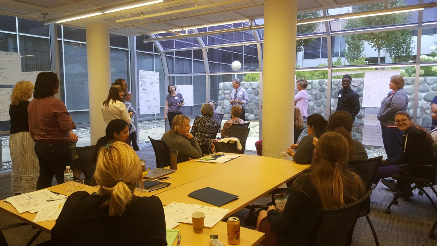 A few people sitting around a conference table and others standing in the background with large posters taped to the windows.