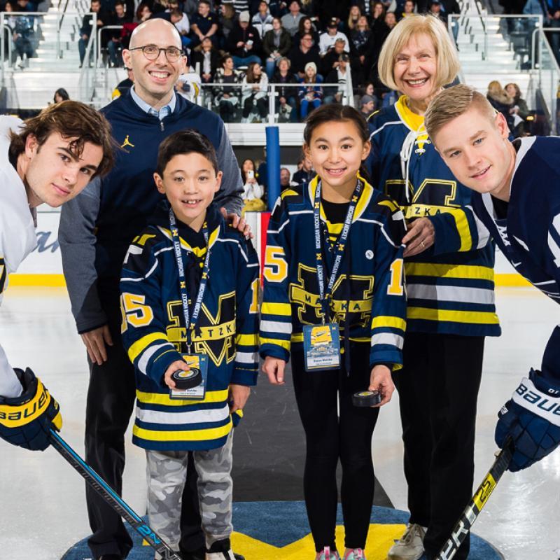 IceALS ceromonial puck drop with Eva Feldman, Stephen Goutman, Scott Matzka's children and team captains from U-M and Penn State