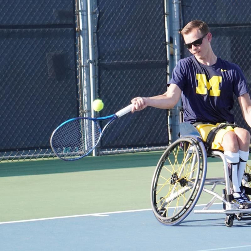 A tennis player rallies the ball back to his opponent.
