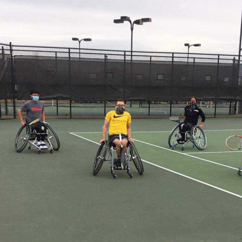 An adaptive tennis team (4 men with athletic wheelchairs) on a tennis court.
