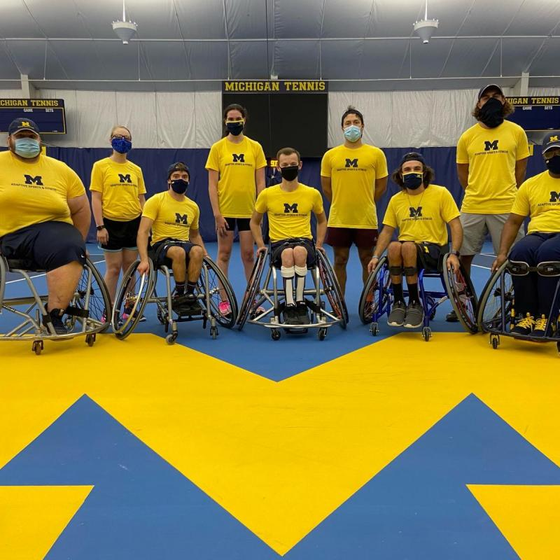 "ASAF Tennis Team - Nine athletes in two rows in masks and yellow t-shirts with Block M's. The athletes in the front row are in wheelchairs and the back row is standing. They are on an indoor U-M tennis court. A sign behind them reads ""Michigan Tennis"""