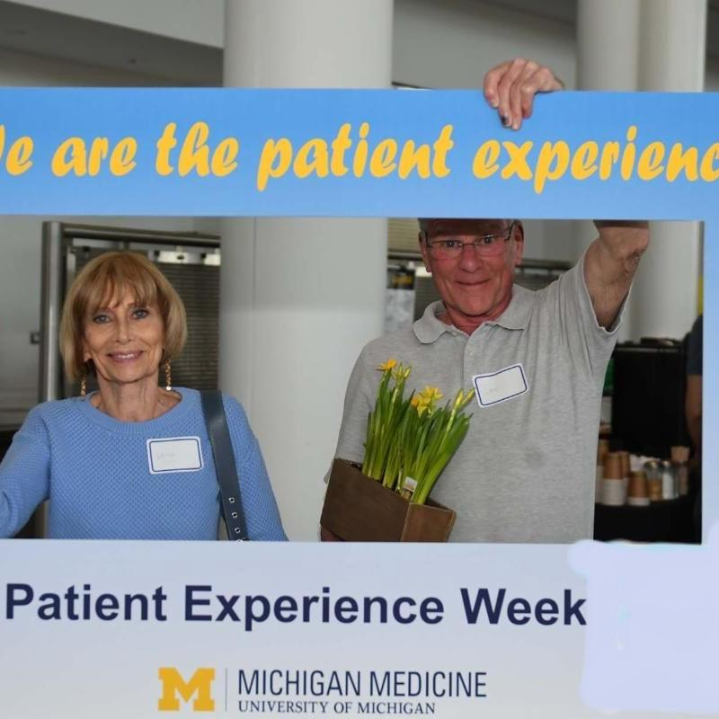 """Two patient and family advisors holding a sign that reads """"I am the Patient Experience"""""""