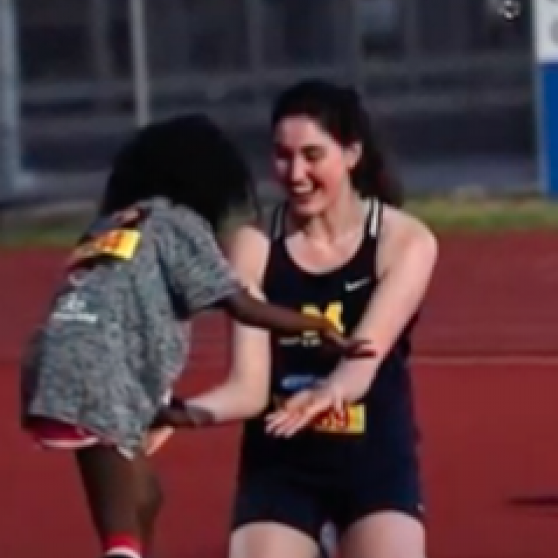 Female U-M Track Athlete kneels on track as a child runs towards her for a hug.