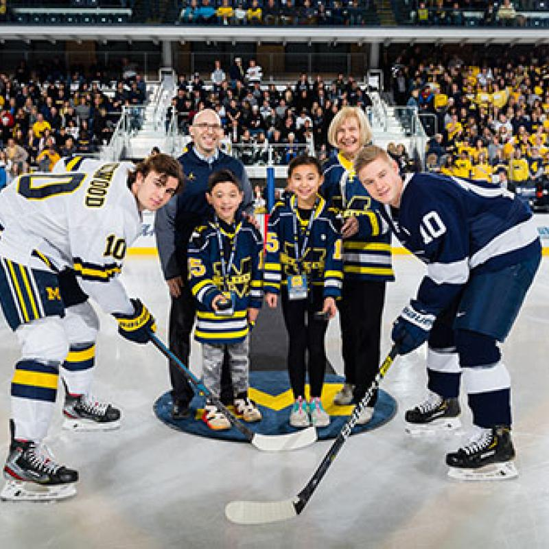 Drs. Goutman and Feldman with Owen and Reese Matzka with U-M and PSU captains