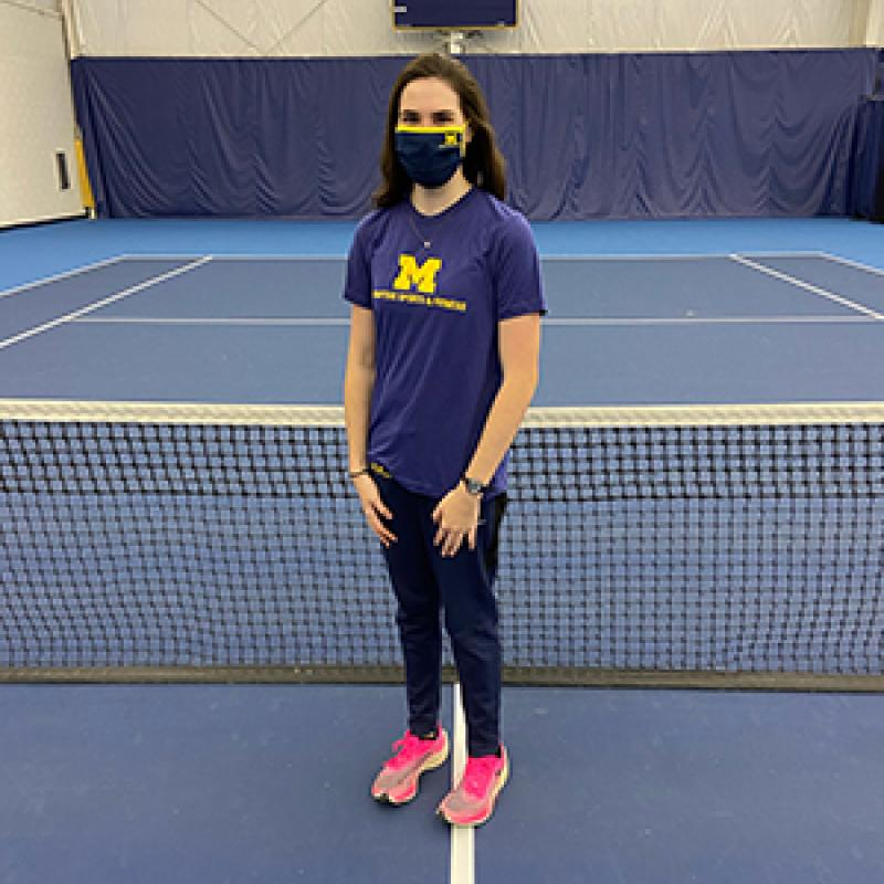 Woman wearing a fabric mask stands in front of a tennis net on a tennis court.
