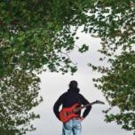 Image of a man with a guitar standing by trees
