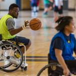 Dr. Okanlami dribbles a basketball as he rolls across a basketball court behind a woman also in a sport wheelchair.