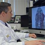 Dr. Alon Kahana in front of a monitor displaying a zebrafish