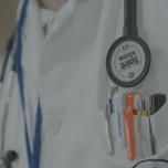 Close up of a stethoscope around a person's neck and pens in the chest pocket of their white coat.