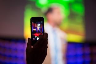 image of smart phone taking photo of ted lecturer