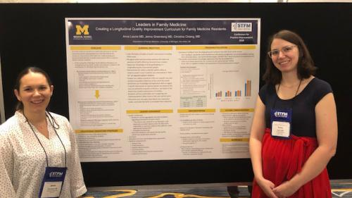 Jenna Greenberg and Anna Laurie stand on either side of a poster titled Leaders in Family Medicine: Creating a Longitudinal Quality Improvement Curriculum for Family Medicine Residents