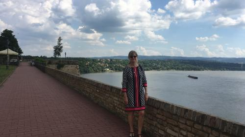 Dr. Djuric stands on a brick path next to a short brick wall. The River Danube is behind her.