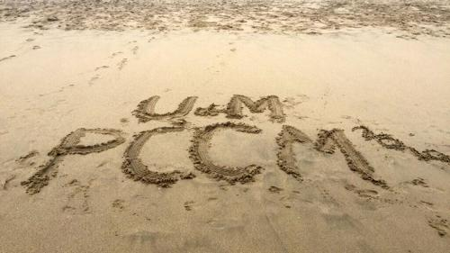 The letters UM PCCM drawn in the sand on a beach