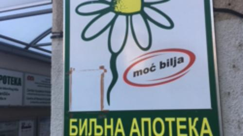 A close up of a sign on a store. The sign has an image of a daisy with a snake sprouting from the center. It features writing in Serbian on it.