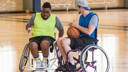 Two basketball players in sport wheelchairs are on a basketball court. One is holding a basketball.