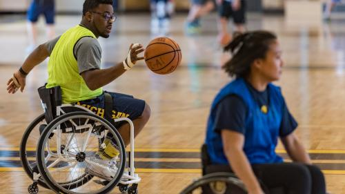 Dr. Okanlami dribbles a basketball as he rolls across a basketball court behind a woman also in a sport wheelchair.