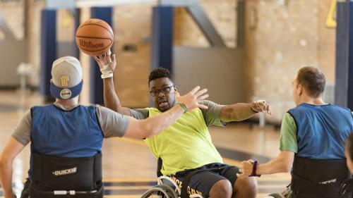Three basketball players in sport wheelchairs are on a court. One has the ball raised in a hand while another blocks.