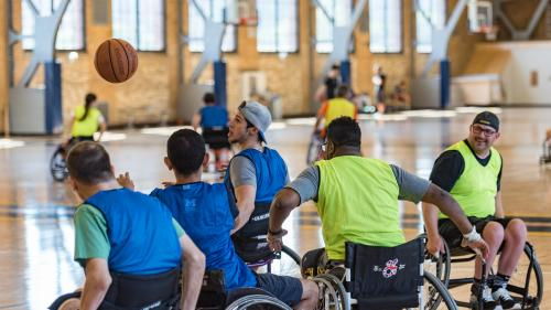 A group of basketball players in sport wheelchairs play a game of basketball on a court. In the background, another group plays on a second court.