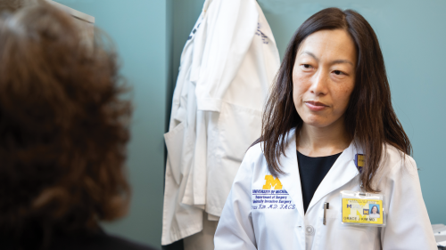 Dr. Grace Kim listening to a patient