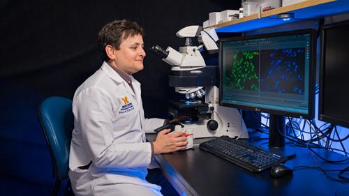 Dr. Jason Miller using the microscope
